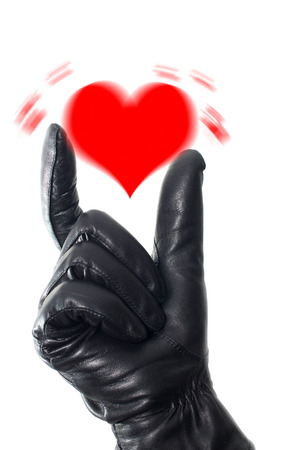 Shaken heart concept with a hand wearing black glove trying to contain the heart photo