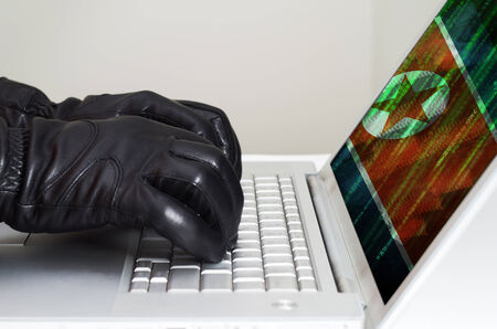 Hacker wearing black gloves using a laptop with North Korea flag in the background
