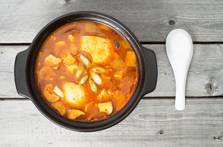 Korean traditional Kimchi soup in a clay pot against wood background Stock Photo