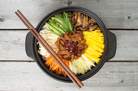 Korean cuisine, beef  Bibimbap in  a clay pot on wooden table Stok Fotoğraf