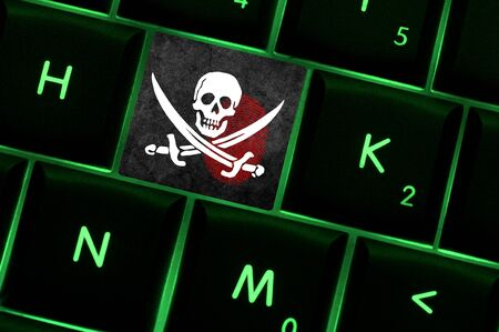 backlit keyboard: Online crime scene with a finger print left on backlit keyboard with pirates flag on it