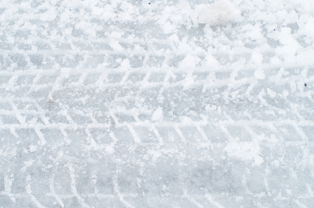 traction: Close up of tire track on icy road Stock Photo