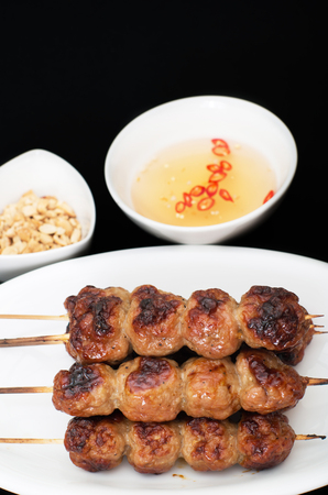 nem: Vietnamese grilled pork meatballs, nem nuong, on black background