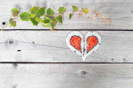 ivy vine: Green ivy vine and two pieces of sushi forming a heart shape on a vintage wooden table Stock Photo