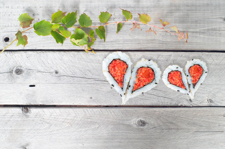 Green ivy vine and two hearts shape forming from four pieces of sushi on a vintage wooden table