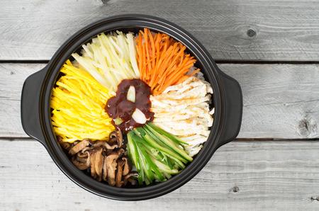 Korean cuisine, vegetarian Bibimbap in  a clay pot on a wooden table