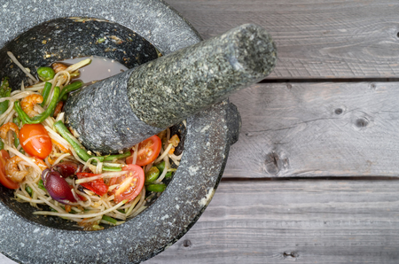 Thai spicy green papaya salad in traditional marble mortar and pestle on wooden table