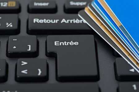 technology transaction: Stack of credit cards on a french keyboard, spending concept