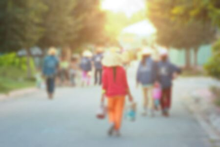 Unidentified Asian workers walking towards the factory. High key blurred image with flare, bleached effect applied