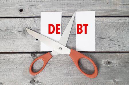 Cut debts concept against a wooden background