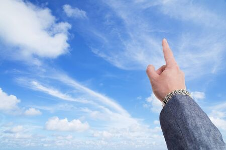 Sky is the limit concept with hand in business suit  pointing toward the sky photo