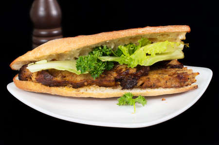 mi: Banh Mi, Vietnamese sandwich filled with pork pate and vegetables on a black background