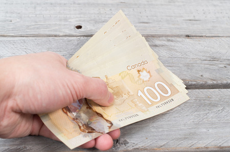 Hand holding a bunch of brown bank notes on a wooden table Stock Photo