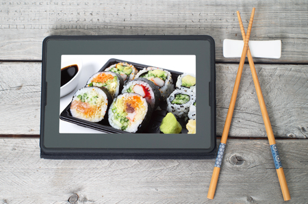 chopsticks: Online Japanese food delivery concept with sushi rolls on an electronic tablet and chopsticks Stock Photo