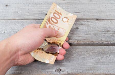 Une main tenant un tas de billets de banque brunes sur une table en bois