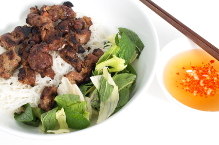 Vietnamese grilled pork skewers on vermicelli and bowl of fish sauce