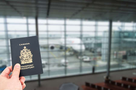 passport background: Hand handing Canadian passport with airplane in background, boarding concept