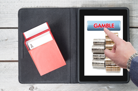texas hold em: Online gambling, technology with mobile tablet on a wooden table Stock Photo