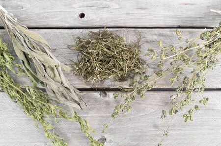 Variety of dried herbs on wooden table