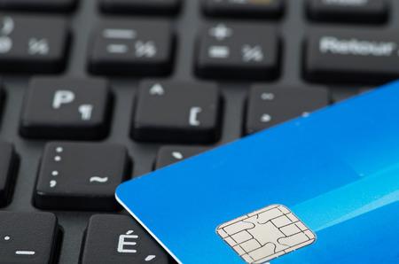 technology transaction: Blue credit card on black keyboard closeup studio shot Stock Photo