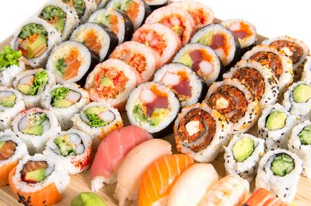 Assorted sushi rolls on a wooden board isolated on white background 版權商用圖片
