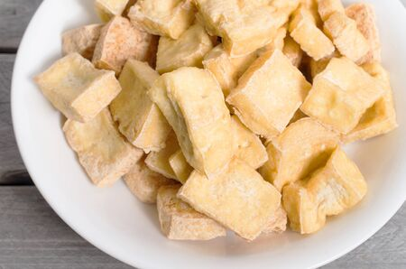 Dee fried tofu cubes on a wooden table, a favorite meal for vegetarians