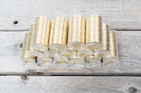 canadian coin: Rolls of golden coins stacked altogether on a wooden table