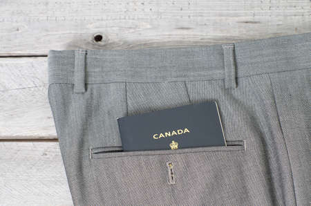 immigrate: Canadian passport in grey pant  back pocket against wooden background, white collar concept