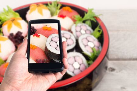 Modern mobile phone used to take pictures of nicely decorated sushi platter Imagens