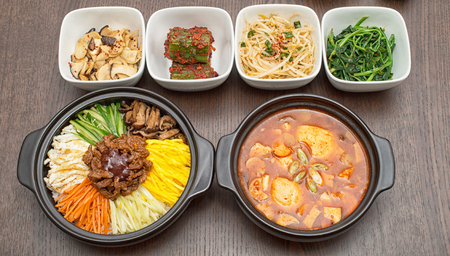 Korean bibimbap and kimchi soup with side dishes on wooden table Stock Photo