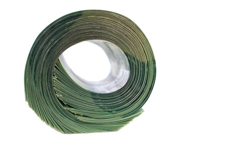 bankroll: Big roll of green banknotes isolated on wooden background