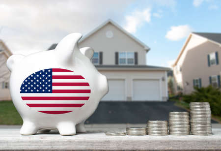 visions of america: American real estate investment concept with piggy bank, stacks of coins and house in the background
