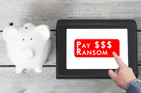 ransom: Businessman paying a ransom to ransomware on a tablet device with piggy bank next to it Stock Photo