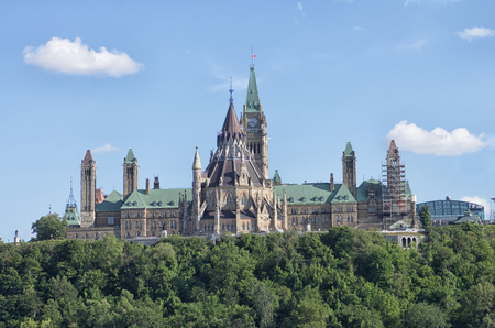 Parliament Buildings with flag flies half mast  and Library, Ottawa, Ontario, Canada