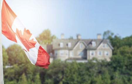Canadian flag waving over 24 Sussex drive in blurred background with flare effect applied Stock Photo