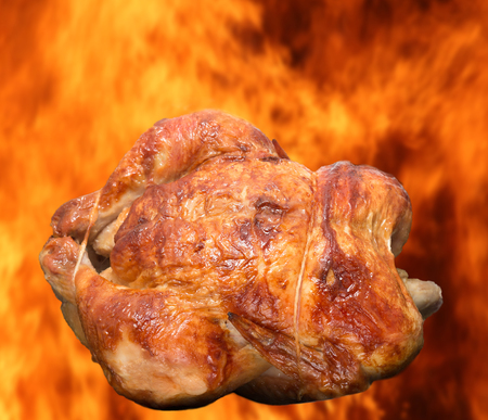 broiled: Roasted chicken isolated against burning flames background, broiled concept