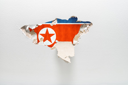 espionage: Hole in gypsum wall showing North Korean flag. industrial espionage concept