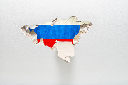 Hole in gypsum wall showing Russian flag. industrial espionage concept