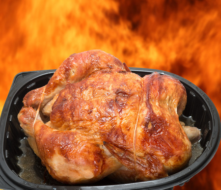 broiled: Roasted chicken in a commercial plastic container against burning flames background, broiled concept