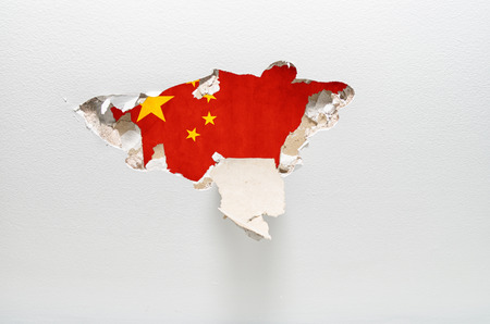 syndicate: Hole in gypsum wall showing Chinese flag. industrial espionage concept