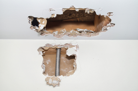 Hole inside gypsum wall showing electrical cords