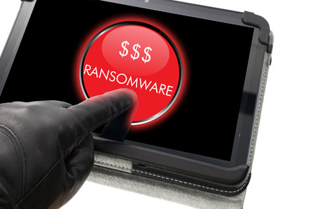 Hacker wearing black glove clicking on ransomware button on a virtual touch screen Stock Photo