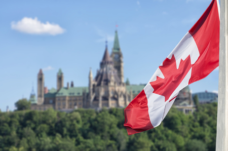 Canadian flag waving with Parliament Buildings hill and Library in the background