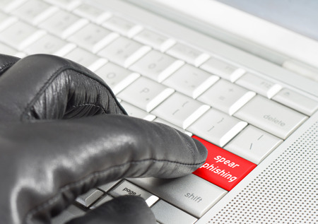 shutdown: Spear phishing concept with hand wearing black leather glove pressing metallic keyboard key