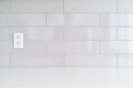 Modern kitchen granite countertop  against gray ceramic backsplash