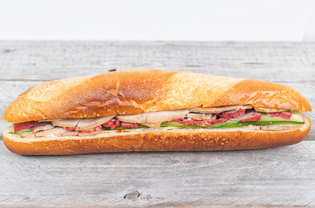 mi: Banh Mi, Vietnamese sandwich filled with pork sausage and barbeque pork on a wooden table Stock Photo