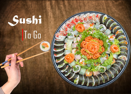 Variety of sushi rolls and sashimi on a plastic platter against wooden background