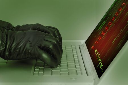 Hacker wearing black gloves using a laptop preparing an attack using ransomware