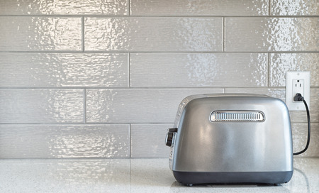 plugged in: Plugged in retro styled toaster with sliced bread against grey ceramic backsplash in background Stock Photo