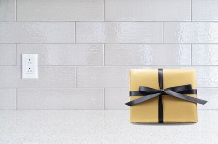 countertop: Modern kitchen granite countertop  against gray ceramic backsplash with a golden gift box